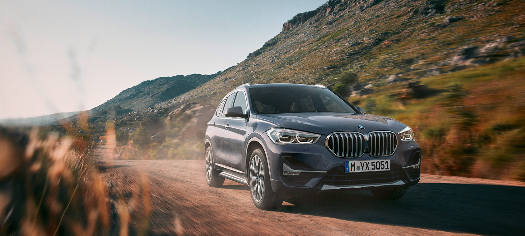 BMW X1, three-quarter front view driving in front of mountain scenery.